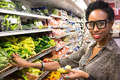 Afro caribbean housewife buying vegetables in a supermarket