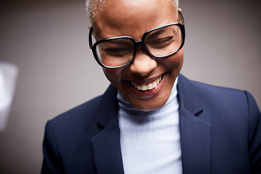 Lifestyle coffee shop made in Barcelona. Afro Caribbean woman, dressed in a suit and wearing glasses, smiling and shy.