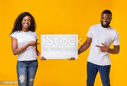 1168002879 istock photo Afro couple is holding white advertising board 1165260162