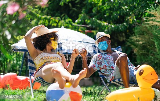 Afro Couple wearing protective face mask having staycation fun on back yard and practicing alternative greeting, during COVID-19
