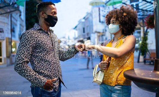 Afro Couple wearing protective face mask walking on the streets and practicing alternative greeting, during COVID-19