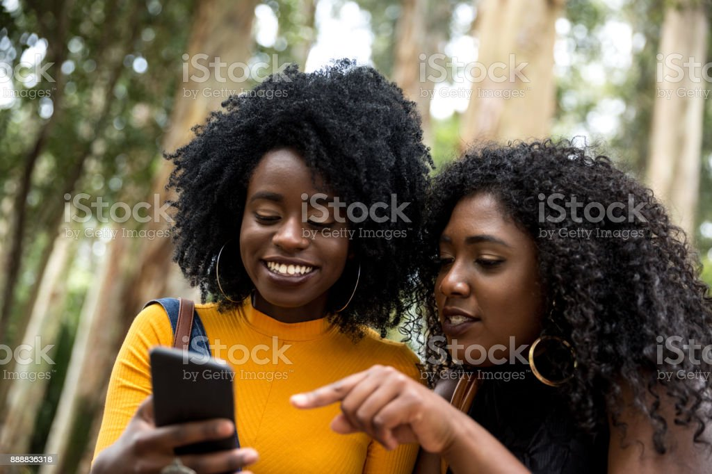 Afro descent girls using smartphone in the park stock photo