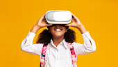istock Afro Elementary Student Girl Using VR Headset, Yellow Background 1172148873