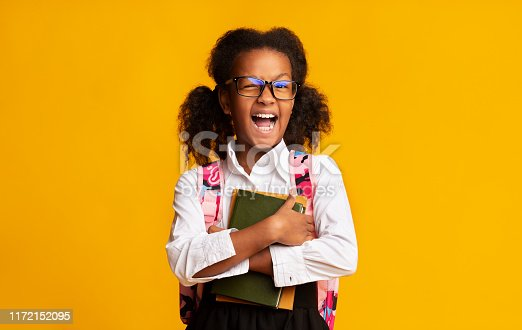 1176772377 istock photo Afro Elementary Student Girl Winking At Camera Over Yellow Background 1172152095