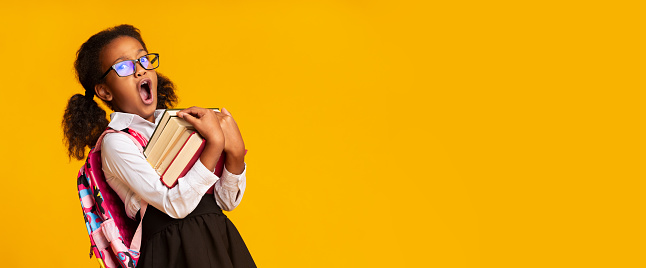 istock Afro Elementary Student Girl Yawning Holding Books, Yellow Background, Panorama 1176772471