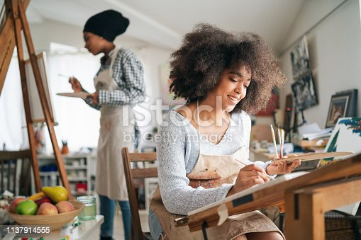 istock Afro Female fine artists drawing in studio 1137914555