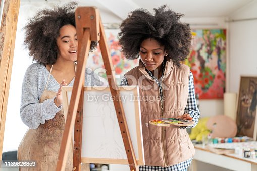 istock Afro Female fine artists drawing in studio 1139826859