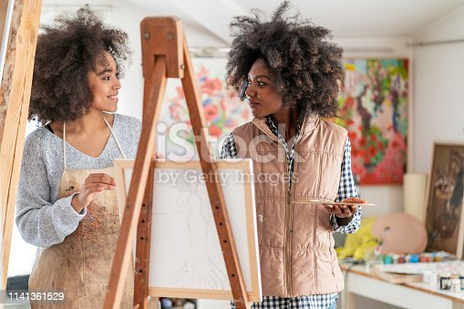 824254912 istock photo Afro Female fine artists drawing in studio 1141361529