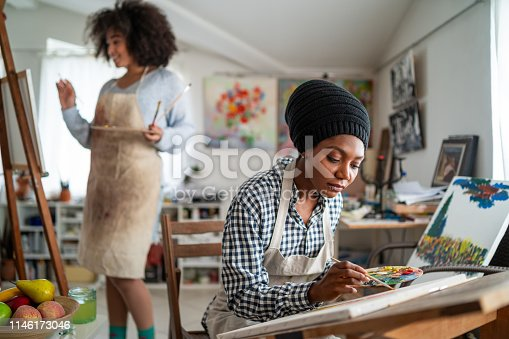824254912 istock photo Afro Female fine artists drawing in studio 1146173046