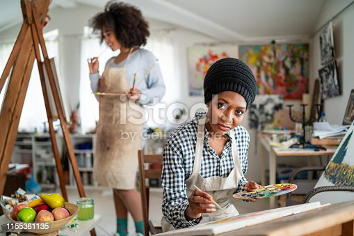 824254912 istock photo Afro Female fine artists drawing in studio 1155361135