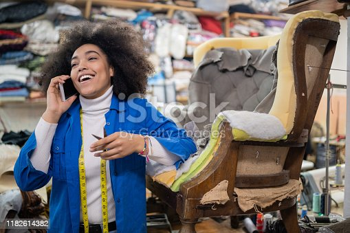 Afro Female Small Business Owner Refurbishing Chair In Upholstery Workshop and talking on smart phone