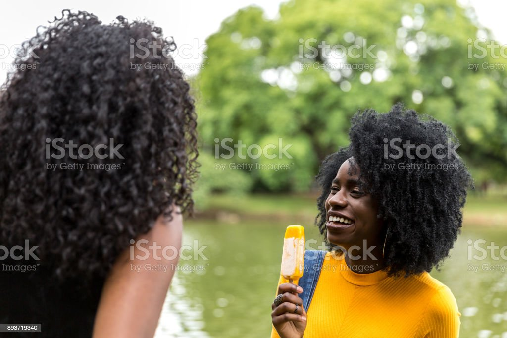 Afro friends enjoy fun ice cream at the the park smiling laughing joy on summer vacation stock photo