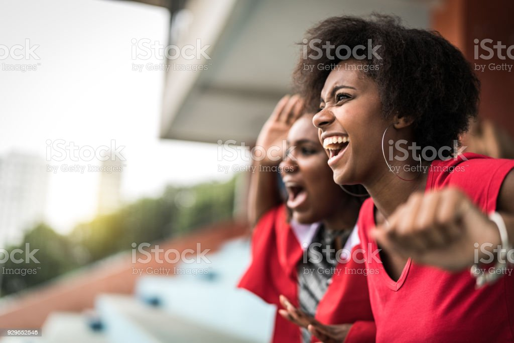 Afro friends watching a soccer game stock photo