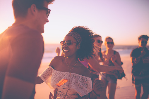 Happy Afro girl dancing on the beach with her boyfriend at an evening beachparty