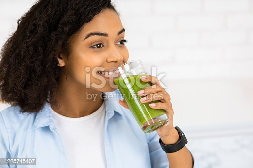 Boost Your Immune System. Headshot of afro woman drinking homemade green juice, looking aside at copy space