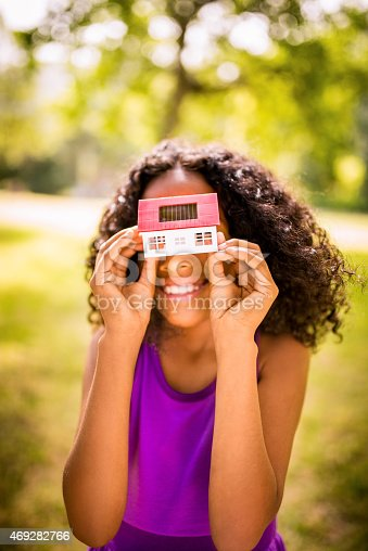 Happy young Afro girl holding an eco friendly toy house with a solar cell on it's roof