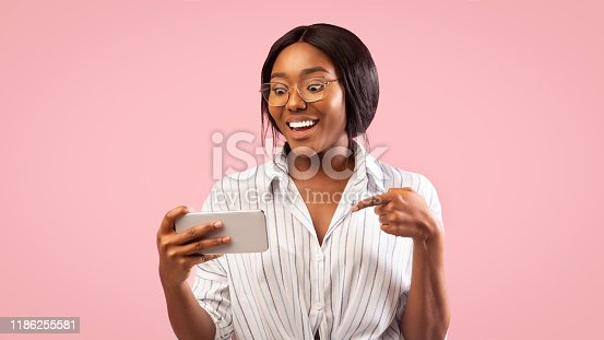 1132512759istockphoto Afro Girl Holding Cellphone Smiling Standing Over Pink Background, Panorama 1186255581