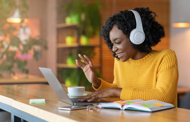 afro girl in headset using laptop, having skype conference - skype imagens e fotografias de stock