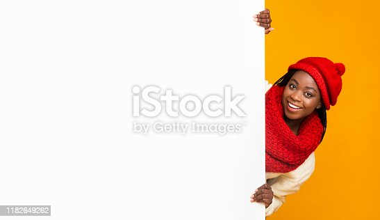 1168002879 istock photo Afro girl in winter set staying next to blank board 1182649262