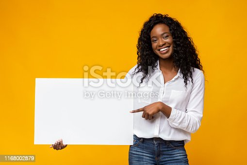 istock Afro girl is holding yellow advertising board 1168002879
