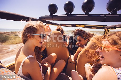 Afro girl laughing in a vehicle with mixed race friends on a summer road trip vacation