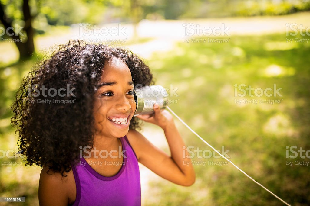 Afro girl listening to a tin can phone in park stock photo
