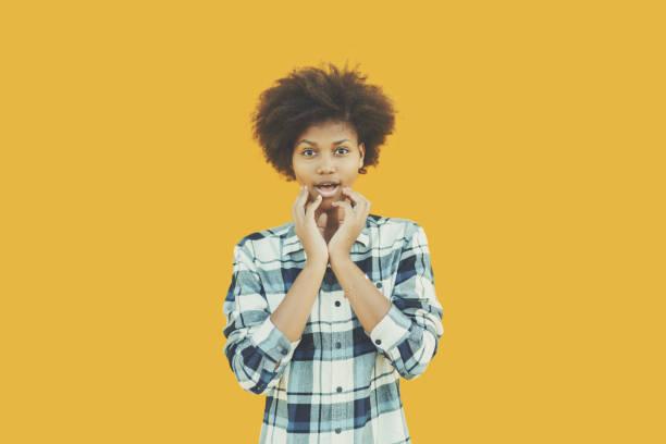 chica afro haciendo cara curioso - sólido fotografías e imágenes de stock
