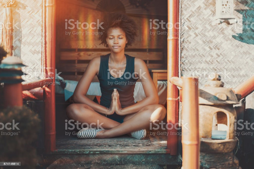 Afro girl meditating with glow over her head stock photo