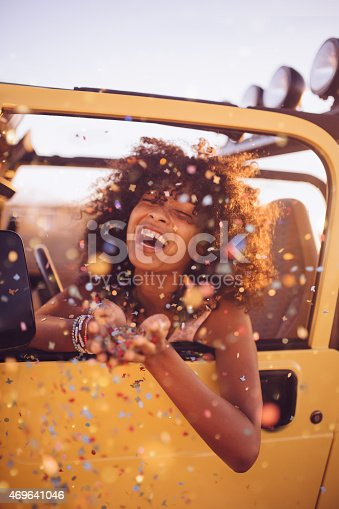 Laughing Afro girl throwing confetti in the back of an open top vacation vehicle on a road trip