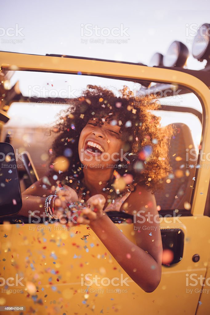 Afro girl on a road trip throwing confetti stock photo
