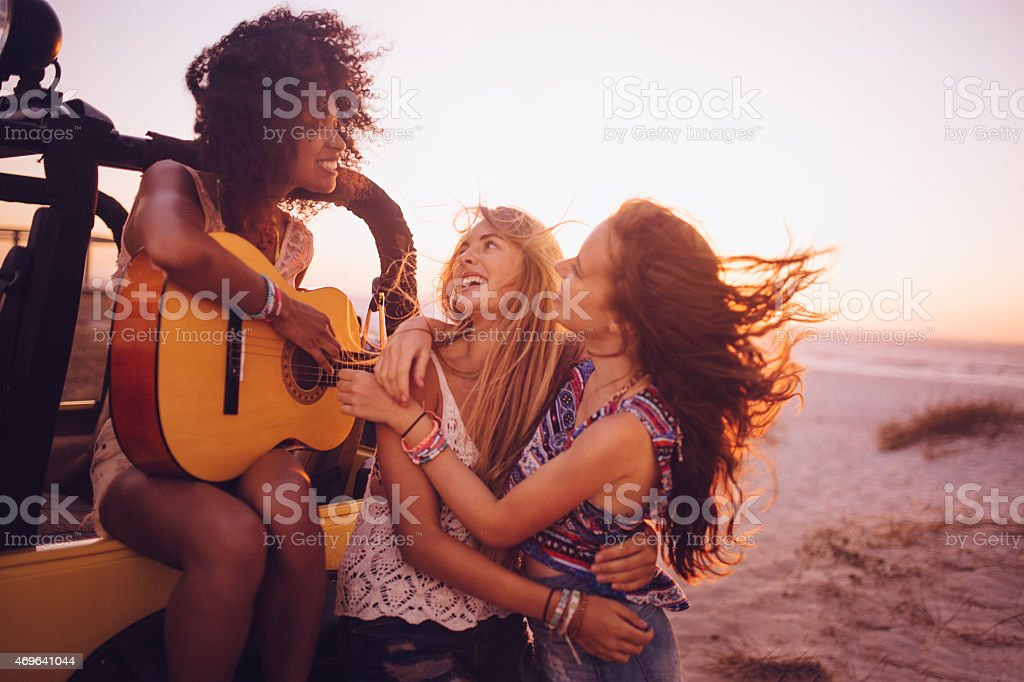 Afro girl playing guitar for her friends at sunset stock photo
