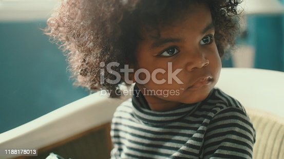 African-american girl(2-3 years) sitting on vintage chair and playing rotary phone, Bangkok Thailand