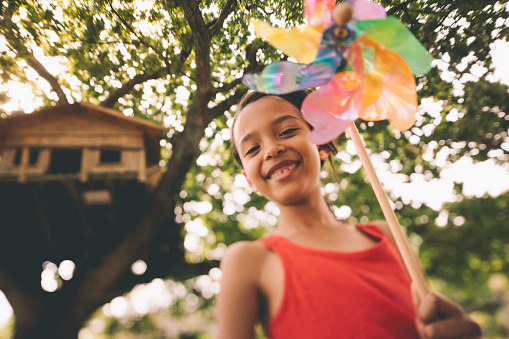 Afro girl playing with a windmill under treehouse in tree