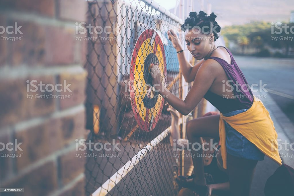 Afro girl trying to illegally climb a fence stock photo