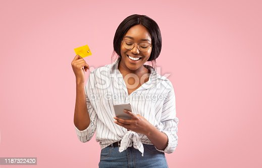 861940002 istock photo Afro Girl Using Cellphone And Credit Card Standing, Studio Shot 1187322420