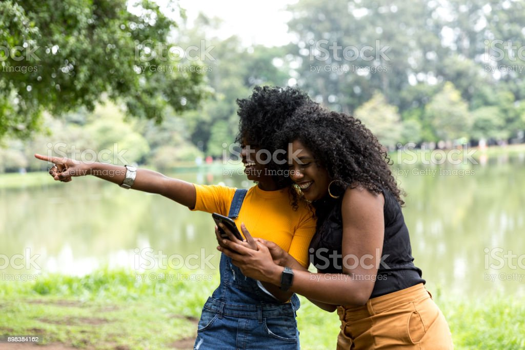 Afro girl using the maps on the phone stock photo