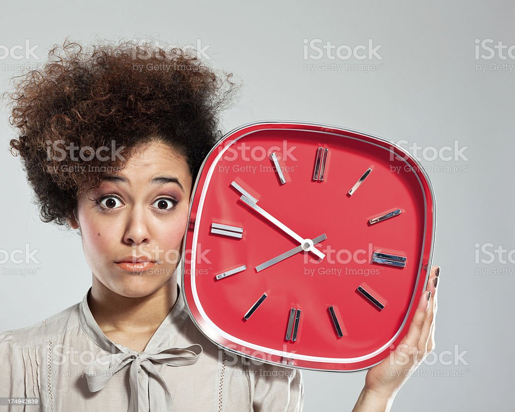 Afro Girl with Clock Portrait of teenaged afro girl holding a big red clock next to her head, staring at the camera. Studio shot, grey background. 18-19 Years Stock Photo