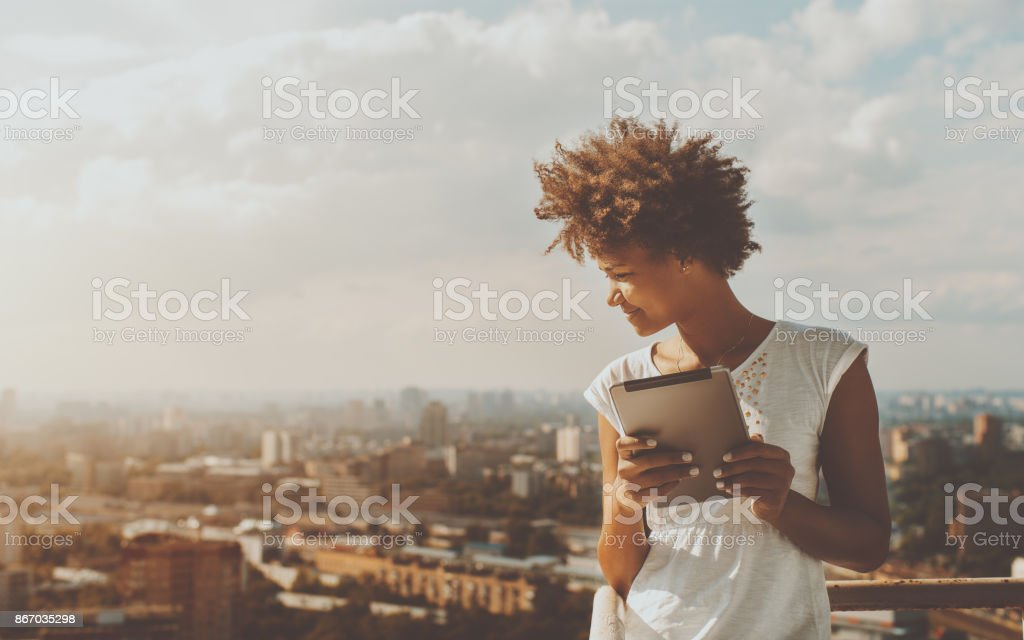 Afro girl with digital pad on observation deck stock photo