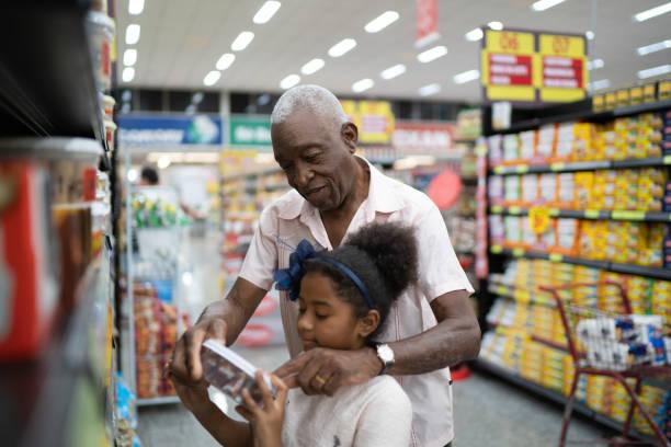 afro großvater und enkelin produkte im supermarkt zu kaufen - kinder verpackung stock-fotos und bilder