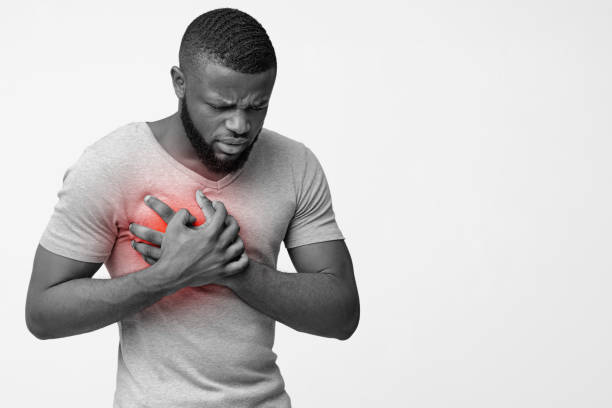 Afro guy holding his chest with hands, having pain Black and white image of african man holding his chest with both hands, having stroke, copy space acute angle stock pictures, royalty-free photos & images