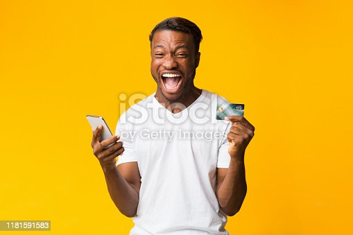 1173546354 istock photo Afro Guy Holding Phone And Credit Card Shouting, Yellow Background 1181591583