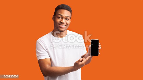 istock Afro guy showing blank black mobile phone screen 1200935504