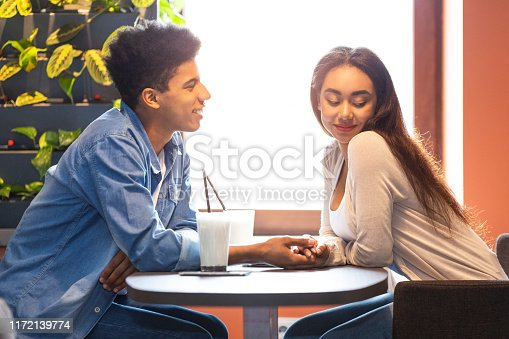 Black Handsome Guy Telling Good Words His Mixed Race Girl, holding hands, cafe interior