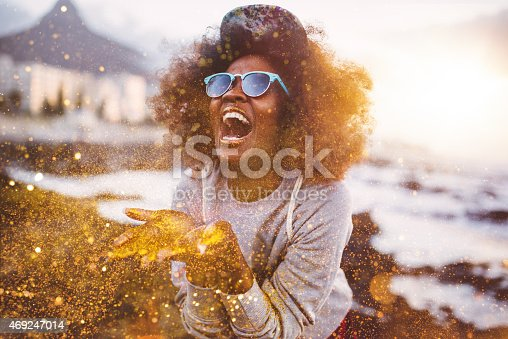 istock Afro hipster girl laughing ecstatically while throwing gold glitter 469247014