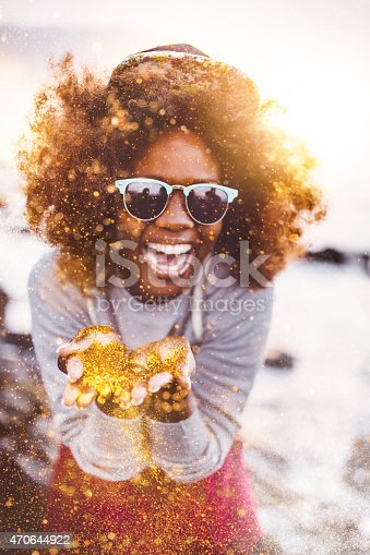 Happy Afro hipster teen laughing outdoors as she is throwing gold glitter toward the camera