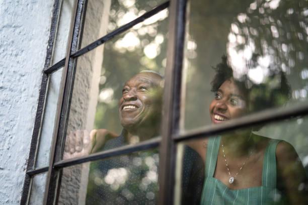 Afro hispanic latino grandfather and granddaughter embracing through the window stock photo