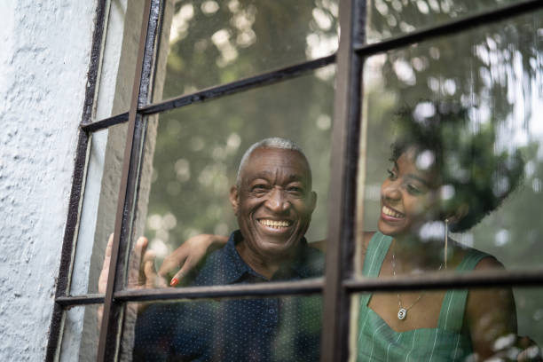 afro hispanic latino grandfather and granddaughter embracing through the window - old men window imagens e fotografias de stock