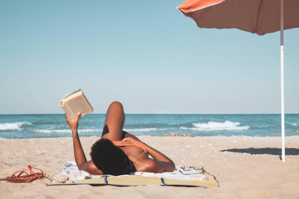 Afro italian woman reading a book and relaxing on the beach in summertime stock photo