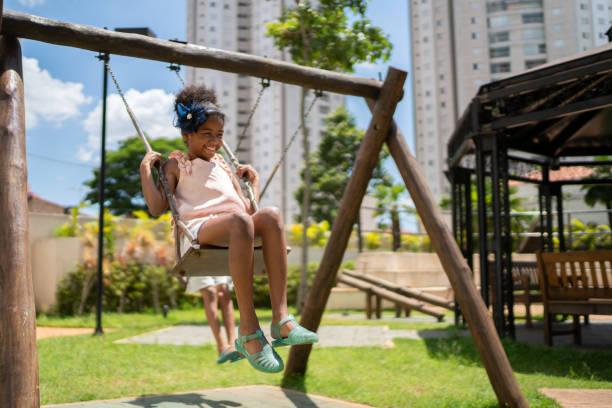 afro latinx children swinging in the playground - aree esterne della scuola foto e immagini stock