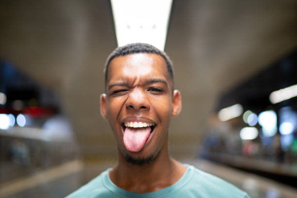 Afro latinx young man making a face at the metro portrait People lifestyle sticking out tongue stock pictures, royalty-free photos & images